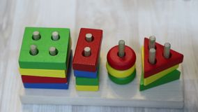 Младенец кладет круг на штырь в деревянный конструктора, замедленное движение Рука годовалого ребенка и игрушка, конец вверх акции видеоматериалы