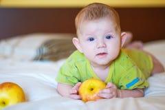 Младенец лежа и держа желтое яблоко стоковое фото rf