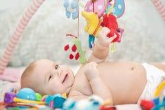 Младенец лежа на превращаясь половике играть в черни воспитательные игрушки Сладостный ребенок вползая и играя с игрушками на ков стоковые изображения rf
