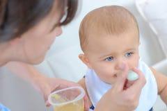 Младенец ложки женщины подавая от пластичной еды бака Стоковые Изображения RF
