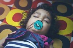 Младенец малыша спать в природе с ниппелью стоковое фото