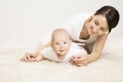 Младенец матери и вползать, младенческий ребенок поднятая голова, активный ребенк стоковое фото