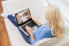 Младенец матери наблюдая видео- монитором на ноутбуке стоковое фото rf