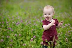 младенец меньший усмехаться лужка Стоковые Фотографии RF