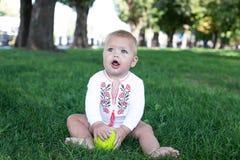 Младенец 11 месяцев месяцев сидя в траве Стоковое Изображение