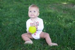 Младенец 11 месяцев месяцев сидя в траве Стоковое Фото