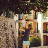 Младенец молодого удерживания матери усмехаясь стоковая фотография