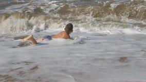 Младенец на пляже, в морской волне мальчик на золотом песке играя в прибое волна с головой покрывает ребенка акции видеоматериалы