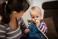 Младенец очищая его нос под наблюдением матери Стоковая Фотография
