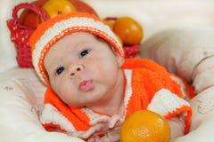 Младенец посылая поцелуй воздуха Портрет newborn младенца в оранжевом knitte Стоковое Фото