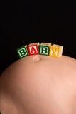младенец преграждает игру говоря деревянное слово по буквам Стоковое фото RF
