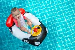 Младенец прорезывание зубов Маленькая девочка более менее чем годовалая управляет раздувной шлюпкой в форме автомобиля В бассейне стоковая фотография rf