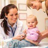 младенец рассматривает стетоскоп педиатра Стоковые Фотографии RF