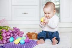 Младенец сидит в кухне Девушка играя пасхальные яйца Концепция Ha Стоковое Фото