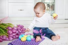 Младенец сидит в кухне Девушка играя пасхальные яйца Концепция Happ Стоковое фото RF