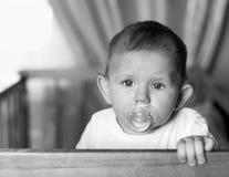 Младенец с куклой в его рте, стоящ в кровати и lookin стоковое фото rf