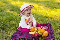 Младенец с плодоовощами на зеленой траве стоковое фото rf
