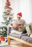 Младенец с усаживанием и использованием отца цифровой таблетки во время рождества Стоковое Фото