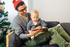 Младенец с усаживанием и использованием отца цифровой таблетки во время рождества Стоковое Изображение RF