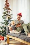 Младенец с усаживанием и использованием отца цифровой таблетки во время рождества Стоковая Фотография RF