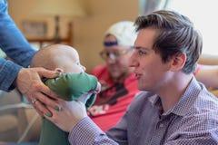 младенец удерживания молодого человека на семье получить совместно стоковая фотография rf