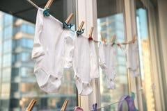 Младенец ягнится одежды получая сух на веревочке с зажимками для белья Стоковые Фотографии RF