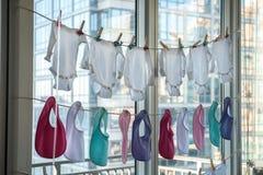 Младенец ягнится одежды получая сух на веревочке с зажимками для белья Стоковые Изображения RF