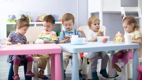 Младенцы питомника есть еду Дети имеют обед в daycare стоковое фото
