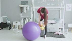 Младенческая девушка уча стоять полагающся на fitball