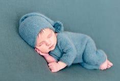 Младенческий ребёнок спать в шерстяном костюме с босыми ногами стоковое изображение rf