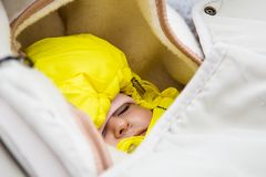 Младенческий сон в детской сидячей коляске в лесе зимы тепло одел желтый комбинезон стоковые изображения