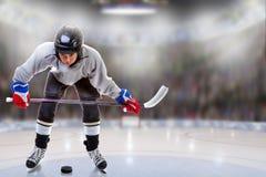Младшая шайба хоккеиста регулируя в арене стоковые фото