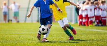 Младшие футбольные команды во время идущего поединка Футбольный матч для игроков молодости стоковая фотография
