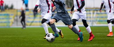 Младший футбольный матч Игра футбола для игроков молодости Мальчики играя футбольный матч на футбольном поле Стоковое Фото