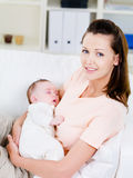 младенец держа newborn slepping женщину Стоковые Изображения