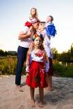 Многодетная семья в этнических украинских костюмах сидит на луге, концепции многодетной семьи стоковое изображение