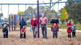 Многодетная семья на парке на Swingset Стоковое фото RF