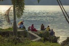 Многодетная семья сидит с рыболовными удочками около зеленых пальм на траве против стоковые фотографии rf