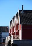 Многоквартирные дома в красной древесине с голубым небом Стоковое Фото