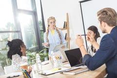 многокультурная группа в составе бизнесмены обсуждая работу пока сидящ на рабочем месте Стоковое Изображение
