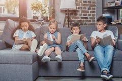многокультурная группа в составе книги чтения детей пока сидящ на софе Стоковые Изображения RF
