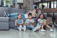 многокультурная группа в составе книги чтения детей Стоковое Изображение RF