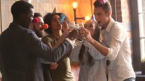 Многокультурное молодые люди clinking стекла и дуя свистки празднуя партию сток-видео