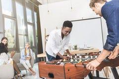 многокультурные бизнесмены играя футбол таблицы пока коммерсантки имея переговор во время пролома стоковые фото