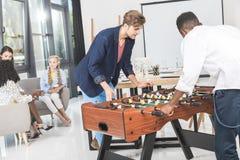 многокультурные бизнесмены играя футбол таблицы пока коммерсантки имея переговор во время пролома Стоковое Фото
