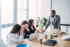 многокультурные бизнесмены имея деловую встречу стоковое изображение