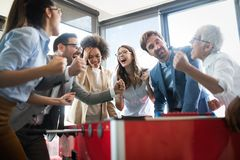 Многокультурные бизнесмены празднуя выигрыш пока играющ настольный футбол стоковое фото