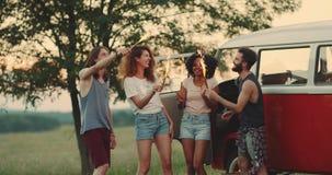 Многокультурные друзья стильные и красивые наслаждающся временем совместно на природе, держащ бенгальские огни и играть видеоматериал