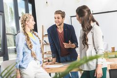 многокультурные молодые бизнесмены имея переговор на рабочем месте стоковая фотография rf