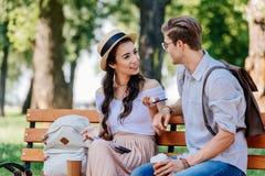 Многокультурные пары имея переговор пока сидящ на стенде стоковое фото
